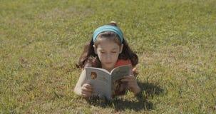 Jeune fille sur l'herbe lisant un livre clips vidéos