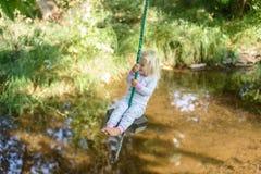 Jeune fille sur l'oscillation d'arbre Photographie stock libre de droits