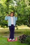 Jeune fille sur l'oscillation de jardin Photographie stock libre de droits