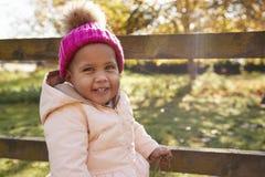 Jeune fille sur la barrière d'Autumn Walk Standing By Wooden photo stock
