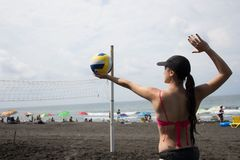 Jeune fille sur la plage de sable jouant le volleyball Photographie stock libre de droits