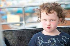 Jeune fille sur la roue de ferris de tour d'amusement de promenade avec l'expression boudante sur le visage Image stock