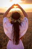 Jeune fille sur le champ de blé faisant le symbole de coeur Photographie stock libre de droits