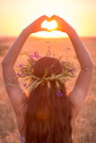Jeune fille sur le champ de blé faisant le symbole de coeur au coucher du soleil Images libres de droits