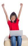 Jeune fille sur le divan avec l'ordinateur portable VII Image stock