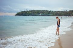 Jeune fille sur le fond bleu de mer Pays tropical Vagues de plage Coucher du soleil aube La Thaïlande Phuket Kata Photographie stock libre de droits