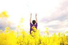 Jeune fille sur un fond des fleurs jaunes de champ photographie stock libre de droits