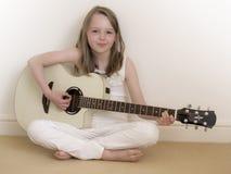 Jeune fille sur une guitare acoustique 2 Photos stock