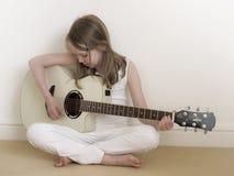 Jeune fille sur une guitare acoustique image libre de droits