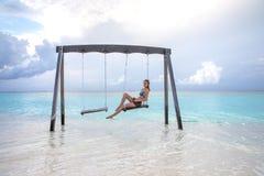 Jeune fille sur une oscillation au-dessus de l'eau Photos stock