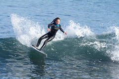 Jeune fille surfant une vague en Californie images stock