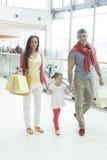 Jeune fille tenant des mains de parents dans le centre commercial Photographie stock
