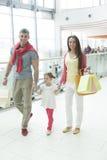 Jeune fille tenant des mains de parents dans le centre commercial Images libres de droits