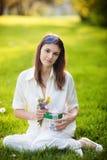 Jeune fille tenant la boîte avec le présent et les fleurs Photos stock
