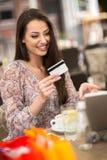 Jeune fille tenant la carte de crédit et faisant des emplettes en ligne Images libres de droits