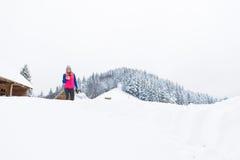 Jeune fille tenant le cottage en bois chaud de station de vacances de neige d'hiver de maison de campagne de café ou de thé de ta Photos libres de droits