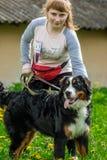 Jeune fille tenant un chien sur un chien de montagne de Bernese de laisse Berner Image libre de droits