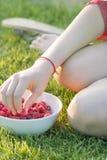 Jeune fille tenant un plat des framboises, se reposant sur l'herbe verte, été, dessert Photos libres de droits