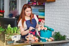 Jeune fille travaillant dans un fleuriste Images stock