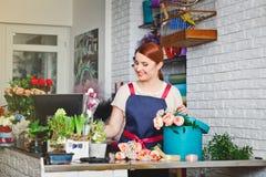 Jeune fille travaillant dans un fleuriste Photos stock