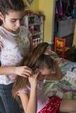 Jeune fille tressant son cheveu d'amis Fille de Criyng pendant les cheveux de tressage photo stock