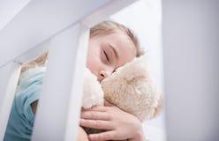 Jeune fille triste étreignant un ours de nounours Images stock