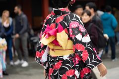 Jeune fille utilisant le kimono japonais se tenant devant le temple de Sensoji à Tokyo, Japon Le kimono est un vêtement tradition photographie stock libre de droits