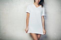 Jeune fille utilisant le T-shirt vide Fond de mur en béton horizontal photos stock