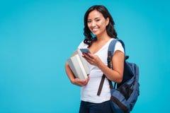 Jeune fille vietnamienne gaie tenant le sac à dos et les livres utilisant le smartphone Photographie stock libre de droits