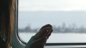 Jeune fille voyageant dans un train et à l'aide du téléphone portable La belle femme envoie un message du smartphone attrayant Image libre de droits