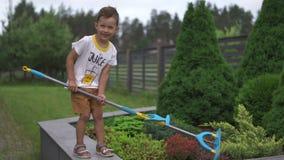 Jeune fils de bébé garçon réduisant des buissons avec un écouvillon de balai dans un jardin avec des jouets - scène chaude d'été  banque de vidéos