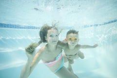 Jeune fils de mère et d'enfant en bas âge nageant sous l'eau dans la piscine et ayant l'amusement Photos libres de droits