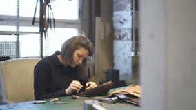 Jeune finissage professionnel femelle pour assembler le sac en cuir foncé banque de vidéos