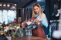 Jeune fleuriste au compteur images stock