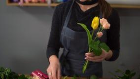 Jeune fleuriste féminin s'chargeant du bouquet moderne à la boutique de fleurs Elle combine les roses crémeuses et les tulipes ja clips vidéos