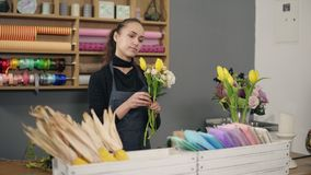 Jeune fleuriste féminin s'chargeant du bouquet moderne à la boutique de fleurs se tenant prêt la table Elle combine les roses cré banque de vidéos
