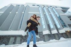 Jeune fonctionnement actif de couples, sautant et appréciant ensemble à l'arrière-plan de ville d'hiver Photo stock