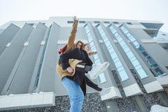 Jeune fonctionnement actif de couples, sautant et appréciant ensemble à l'arrière-plan de ville d'hiver Images stock