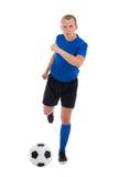 Jeune footballeur attirant dans la boule de coup de pied bleue d'isolement dessus Photos libres de droits