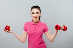 Jeune formation asiatique de femme musculaire et pomme de main avec les haltères rouges, kilogramme Image stock