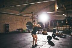 Jeune formation musculaire de femme avec le barbell lourd Photos stock