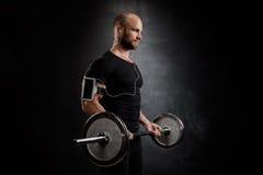 Jeune formation puissante de sportif avec le barbell au-dessus du fond noir images stock