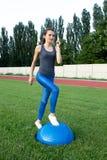 Jeune formation sportive de femme avec la boule de bosu au stade Photographie stock libre de droits