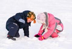 Jeune frère et soeur jouant dans la neige Photographie stock