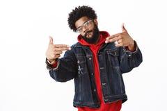 Jeune frappeur masculin d'afro-américain bel frais et stlyish avec la barbe et perçage montrant des gestes d'arme à feu de doigt photographie stock libre de droits