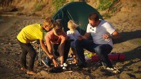 Jeune friture de famille la guimauve sur des brochettes sur le feu près de la tente le jour d'été banque de vidéos