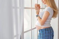 Jeune future mère appréciant la boisson chaude Photos libres de droits