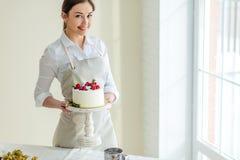 Jeune gâteau d'anniversaire de sourire de participation de mère photographie stock libre de droits
