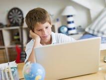 Jeune garçon à l'aide d'un ordinateur portatif dans sa chambre à coucher Photographie stock libre de droits