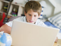 Jeune garçon à l'aide de l'ordinateur portatif dans sa chambre à coucher Images stock